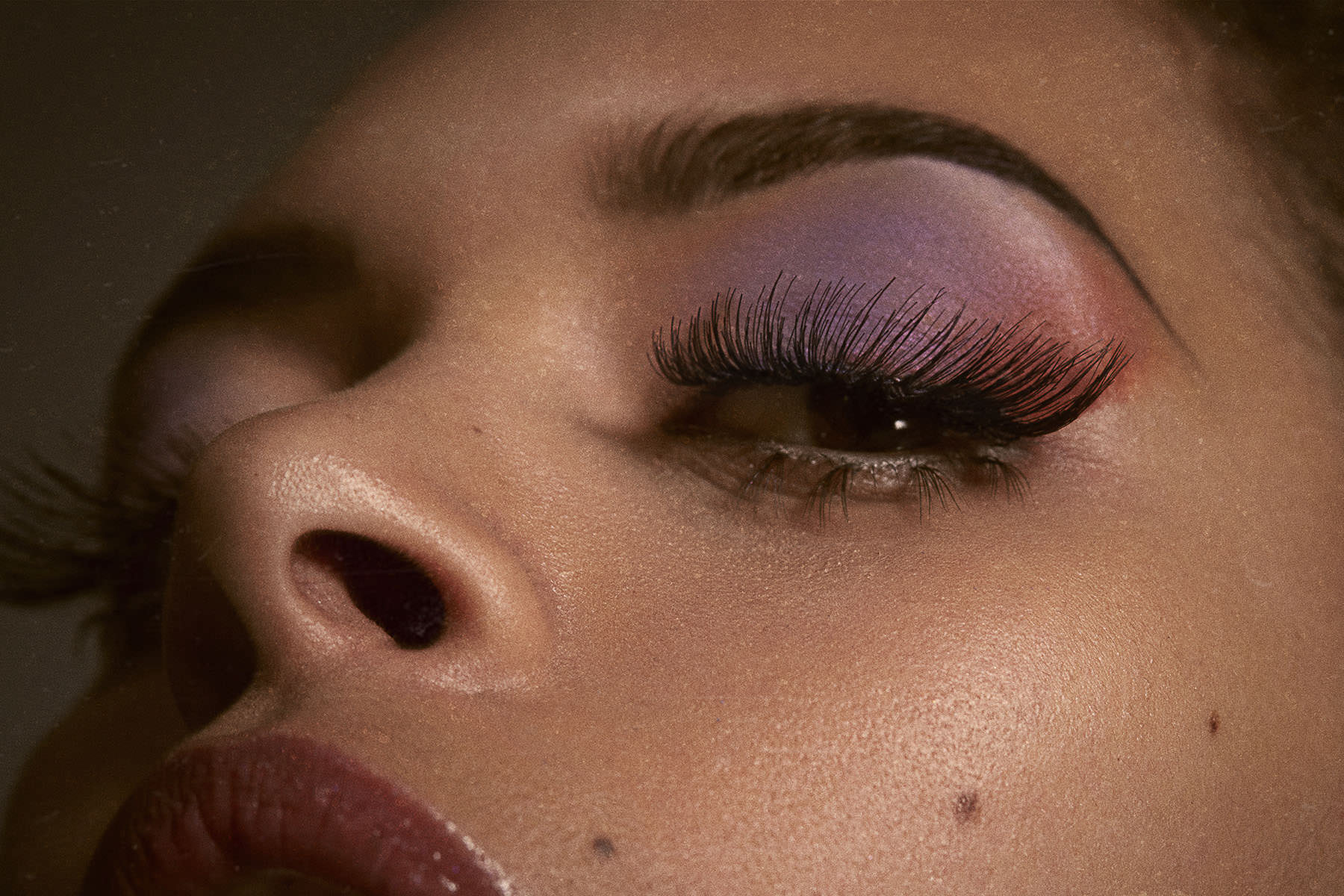 Close-up of a woman with purple eyeshadow and long lashes